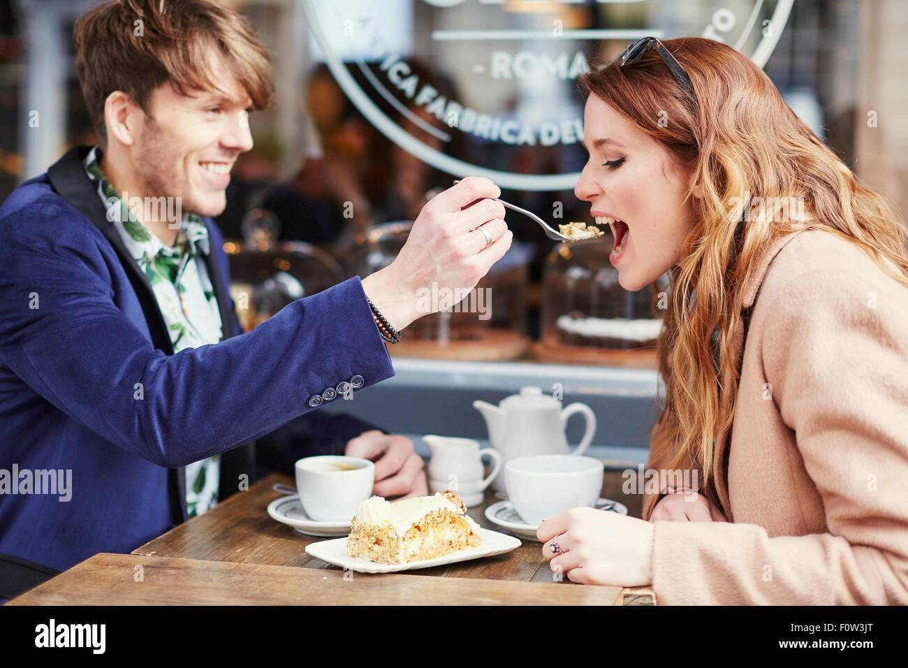 El hombre alimenta pastel a novia a café en la acera, Londres, Reino Unido. Imagen De Stock