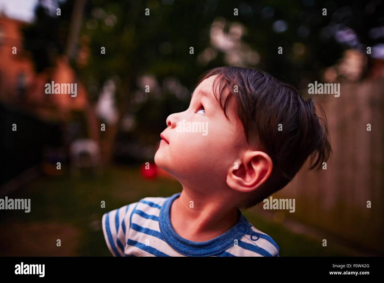 Niño mirando hacia arriba en el cielo Imagen De Stock
