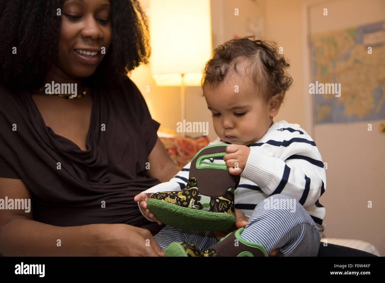 A mediados de mujeres adultas y niños pequeños curiosos hija con un bebé boot Imagen De Stock