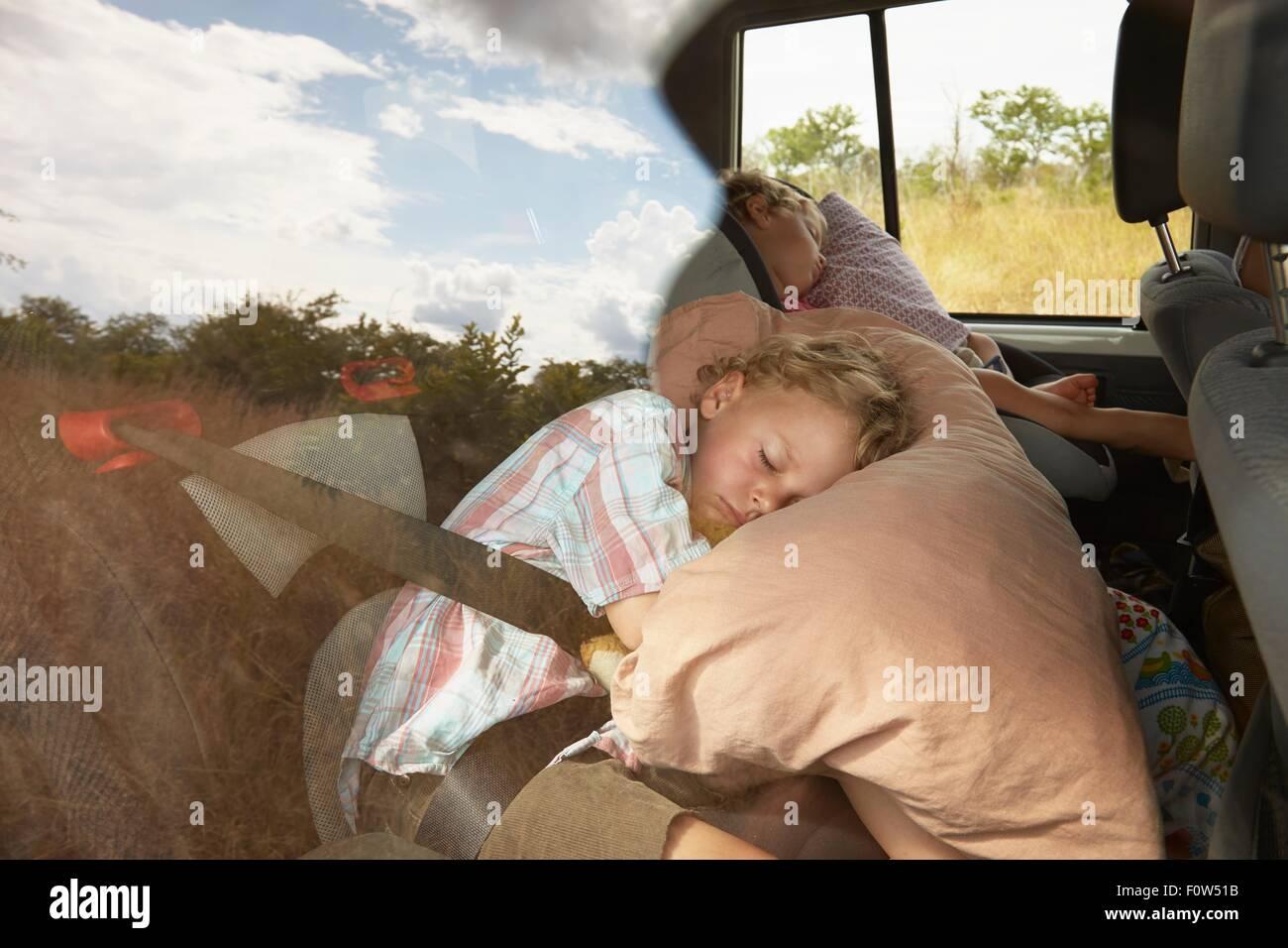 Dos niños dormidos en la parte trasera del vehículo fuera de carretera Imagen De Stock