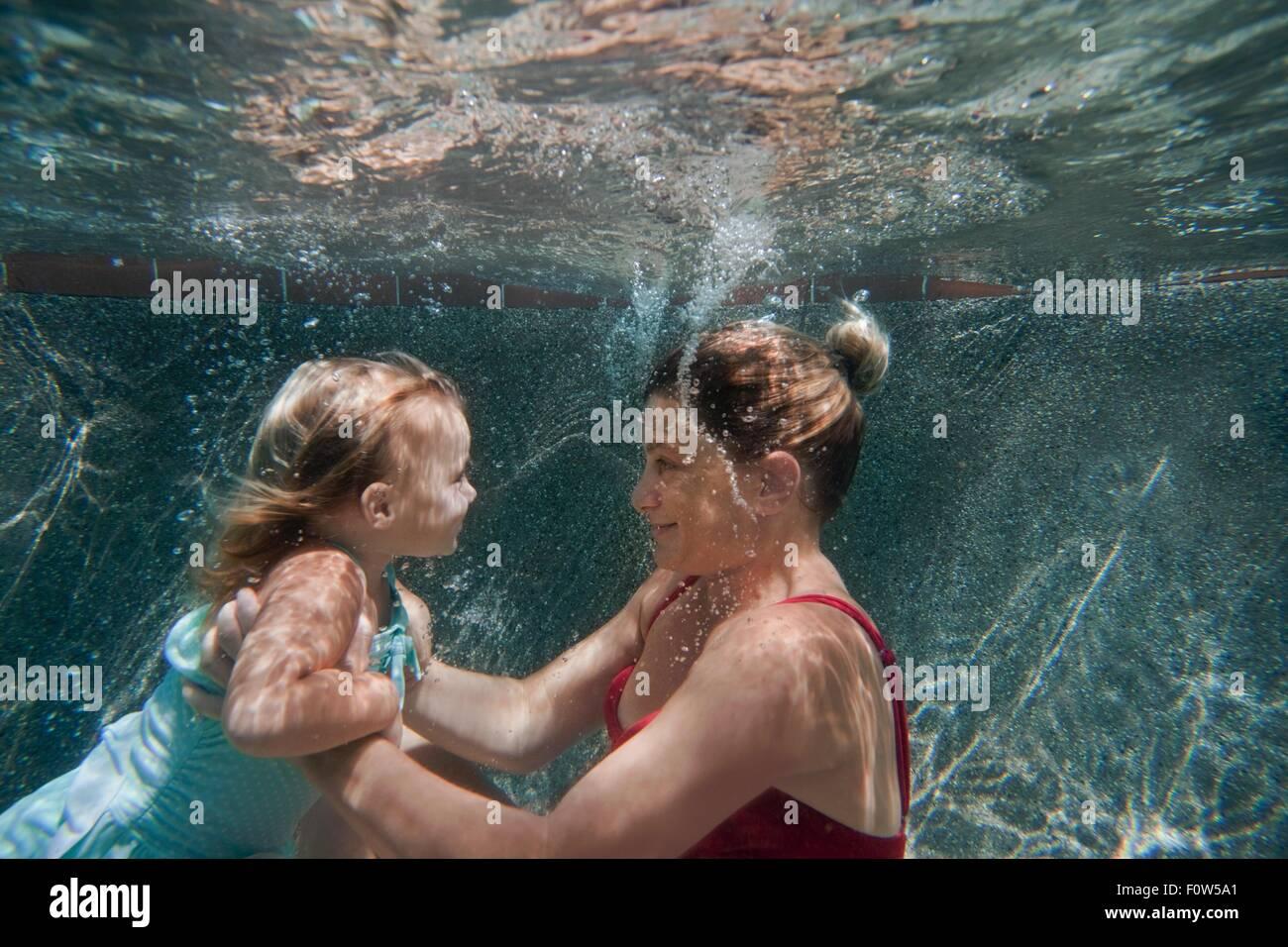 Filmación subacuática de madre sosteniendo hija y ayudarla a aprender a nadar Imagen De Stock