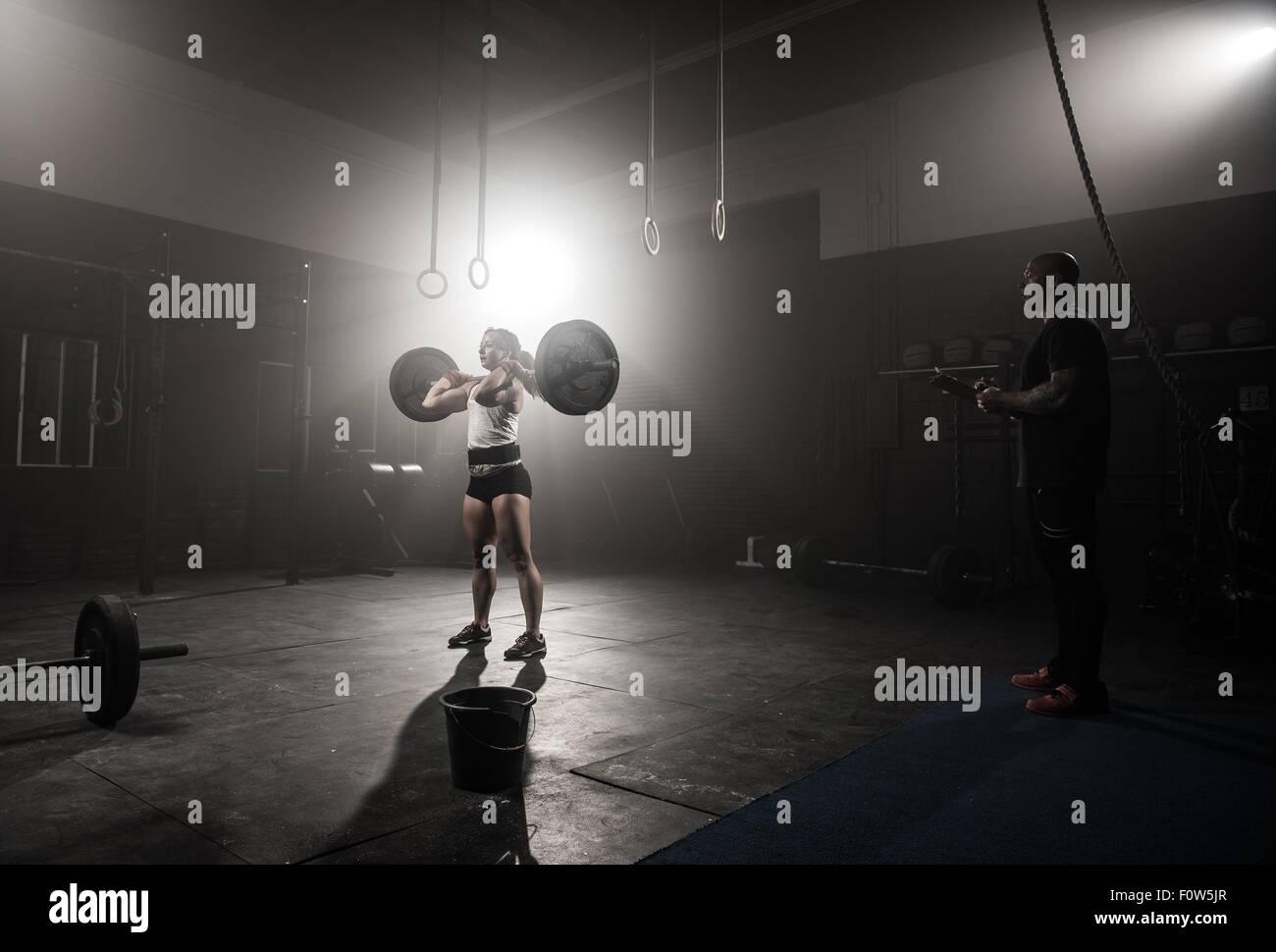 Mujer joven levantando barbell, mientras mira formador Imagen De Stock