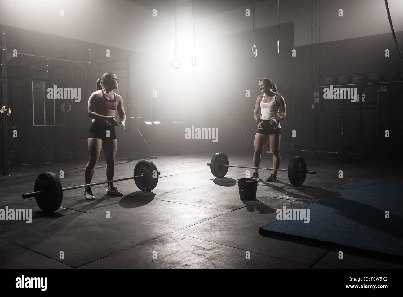 Dos jóvenes mujeres preparando para levantar barras Imagen De Stock
