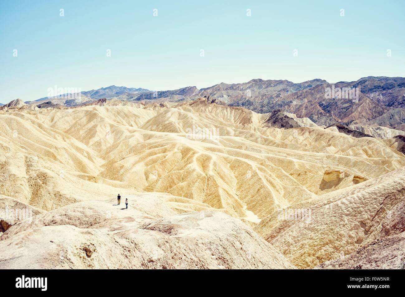 Vista de dos turistas en Zabriskie Point, el Valle de la Muerte, California, EE.UU. Imagen De Stock