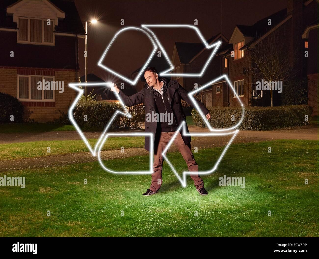 Luz artista pintar un símbolo de reciclaje en el parque Imagen De Stock