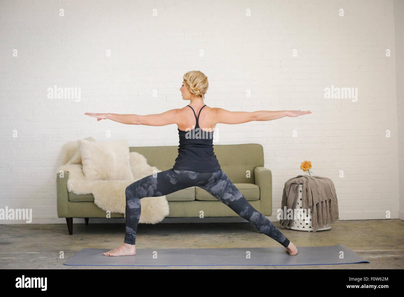 Una mujer rubia en un leotard negro y calcetas de pie sobre una estera del yoga en una habitación, piernas Imagen De Stock