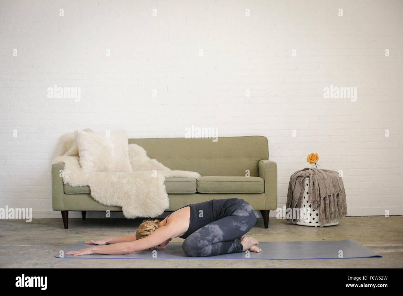 Una mujer rubia, arrodillado sobre una estera del yoga en una habitación, hacer yoga, su brazo estirado en Imagen De Stock