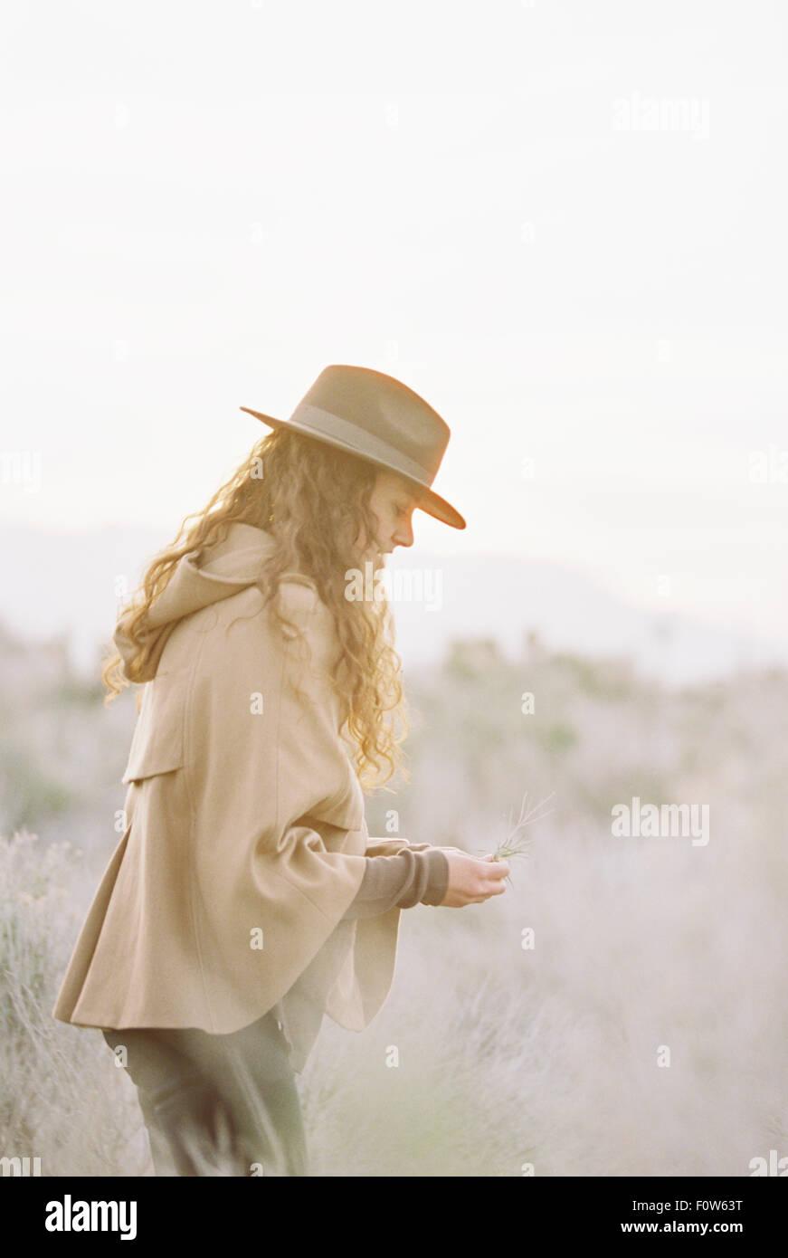 Una mujer con un buen abrigo y un sombrero recogiendo flores silvestres. Imagen De Stock