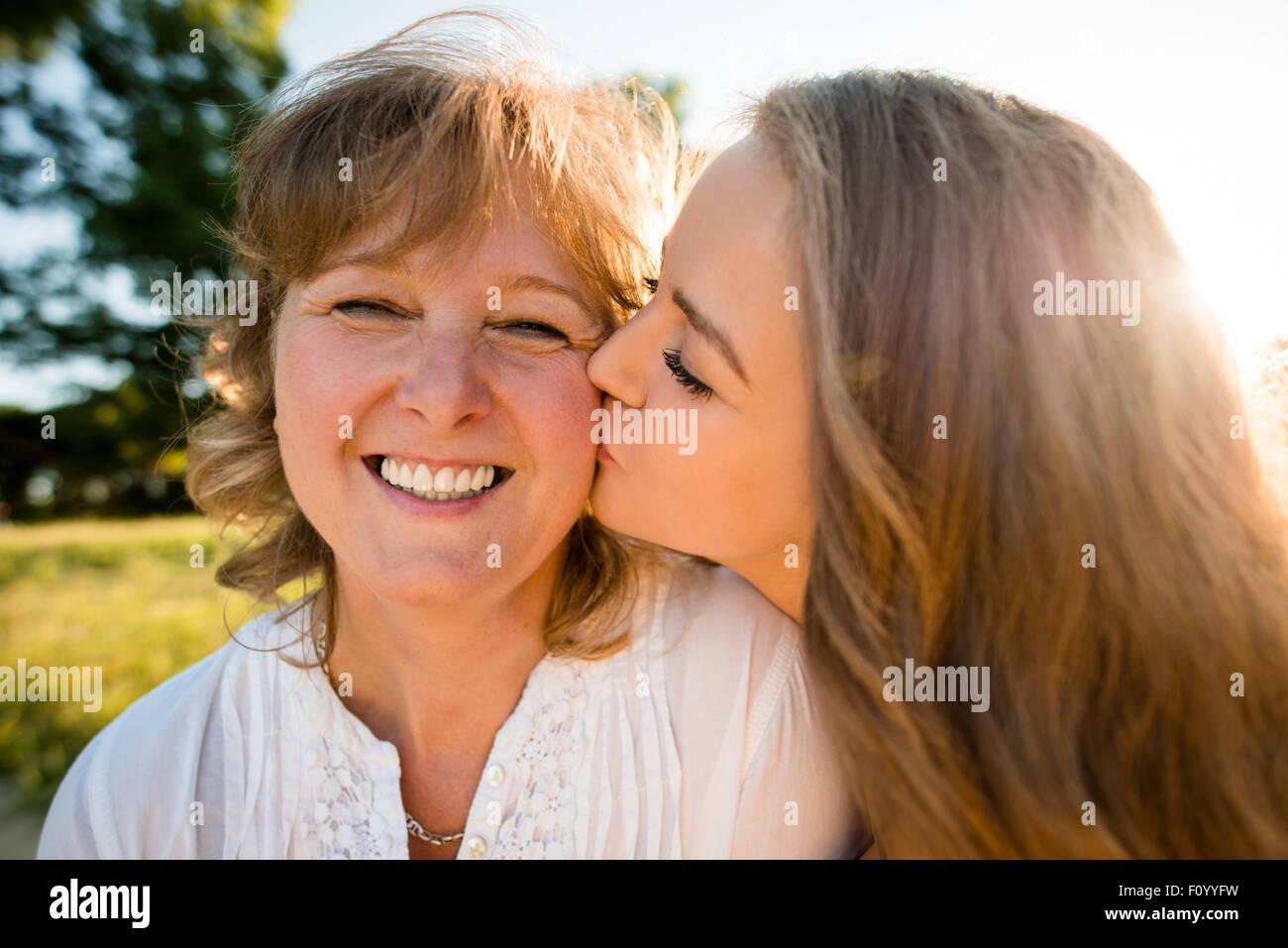 Hija adolescente besando a su madre en la naturaleza al aire libre con el sol en el fondo, gran angular Imagen De Stock