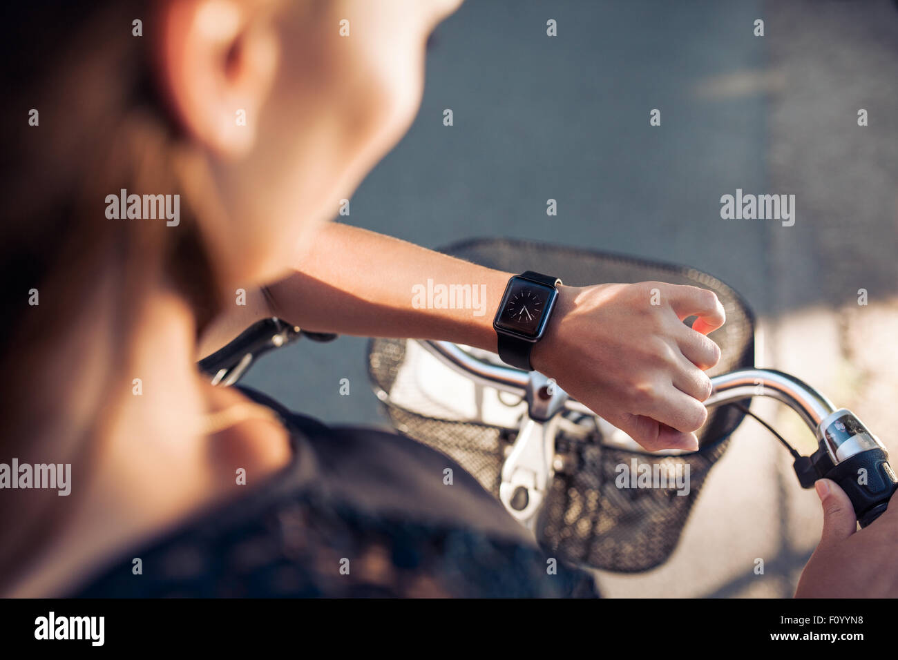 Mujer con una bicicleta mirando su smartwatch. Primer plano de control femenino sobre sus relojes de pulsera inteligente. Imagen De Stock