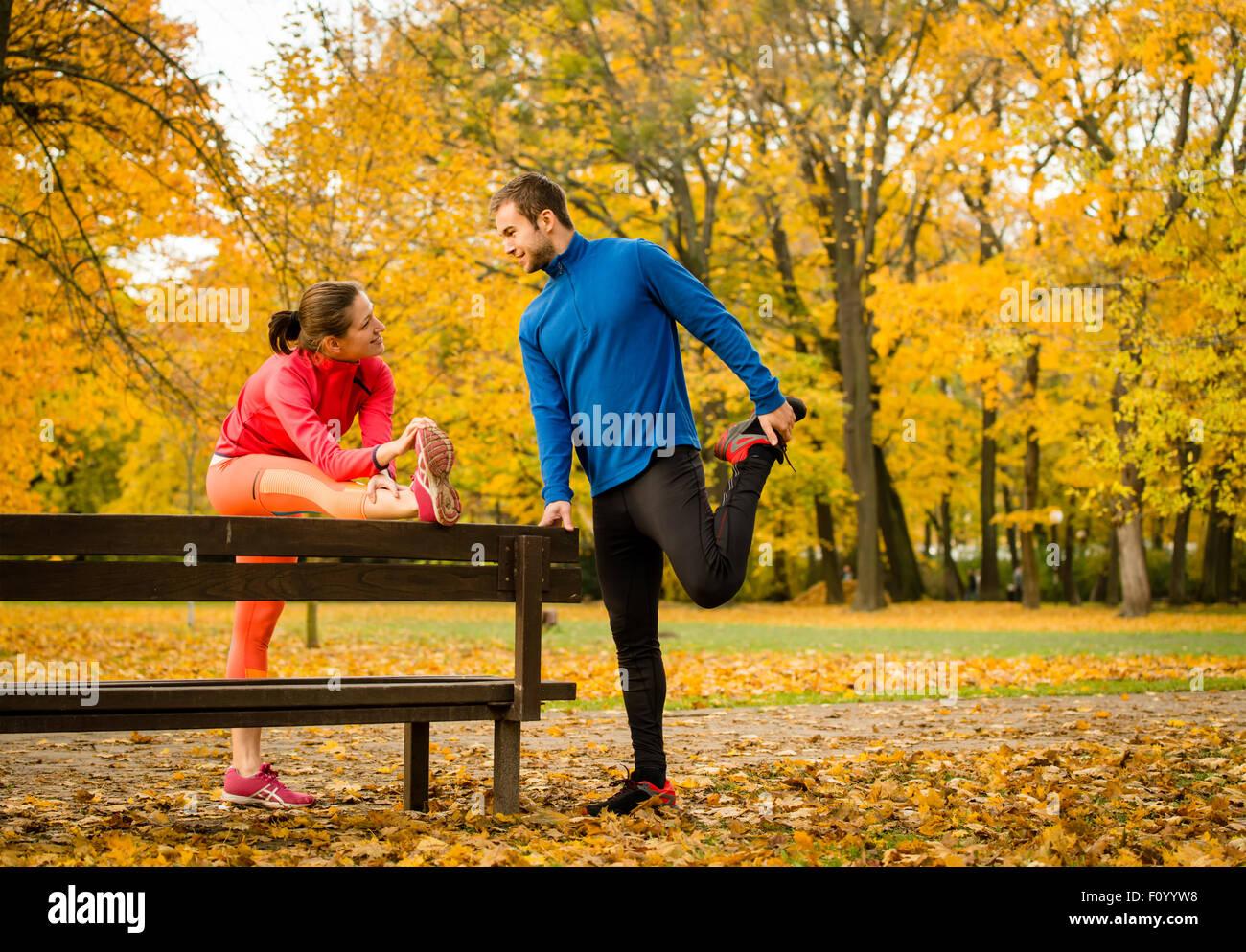 Pareja joven estirando los músculos en un banco antes de correr en otoño la naturaleza Foto de stock