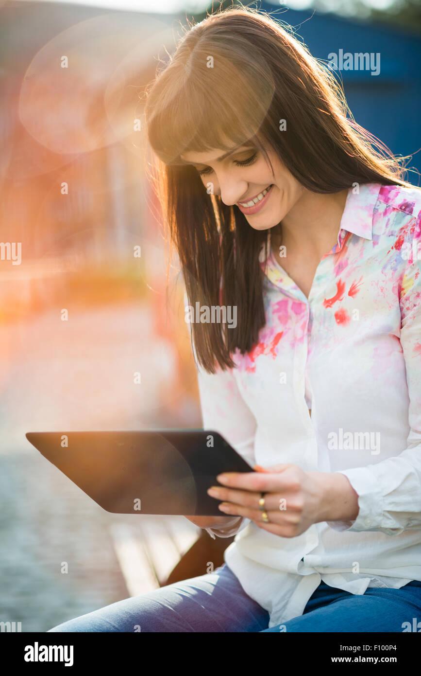 Hermosa joven mujer sentada en un banco en la calle y navegar por internet en tablet pc Imagen De Stock