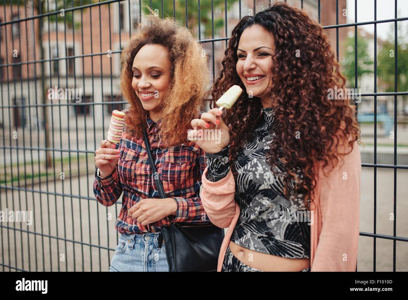 Alegres jóvenes comer helado de caramelo. Dos jóvenes mujeres de pie contra una valla, sonriente, al aire Imagen De Stock