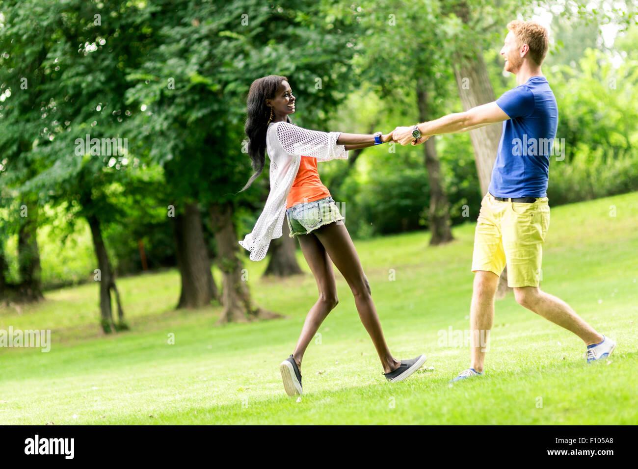Hermosa pareja bailando al aire libre en un parque mostrando la alegría y el amor Imagen De Stock