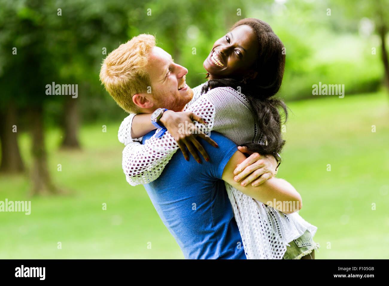 Retrato de una pareja feliz bailando y abrazando en un parque al aire libre Foto de stock