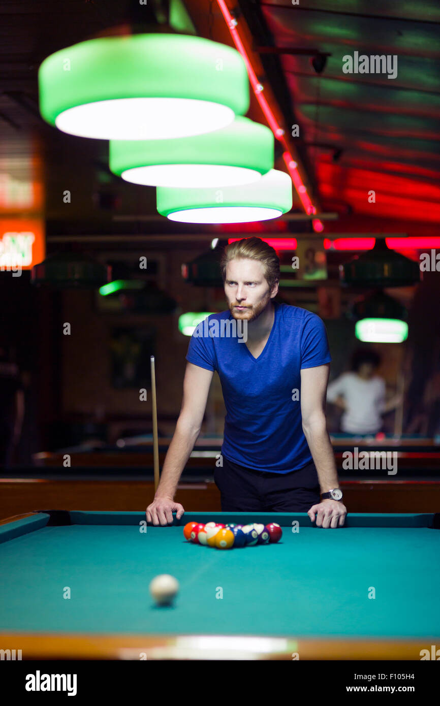 Apuesto joven jugador de billar doblado sobre la mesa en un bar, con una bella iluminación ambiental Imagen De Stock