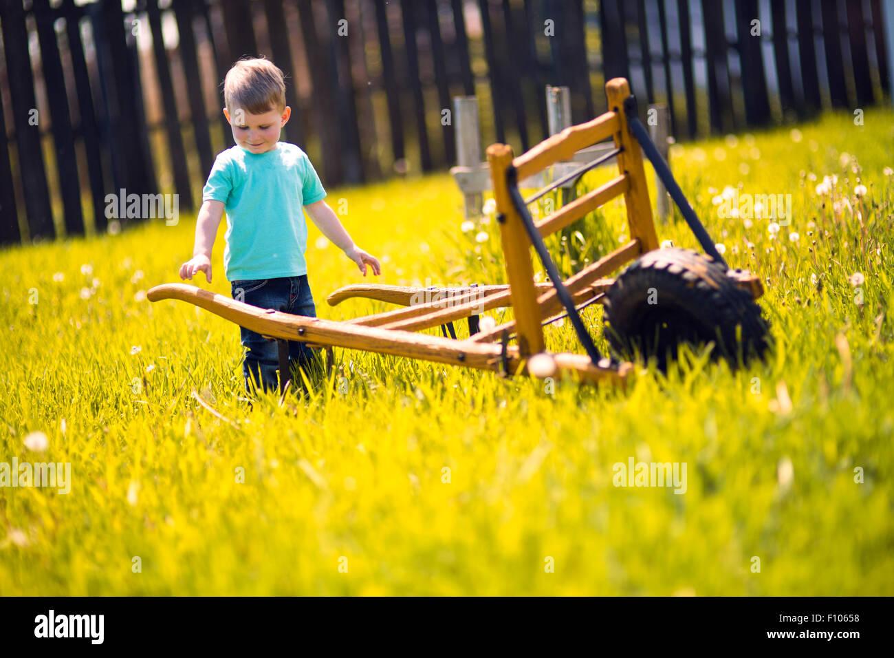 Chico trabajando en los campos y empujando una carretilla de mano Imagen De Stock