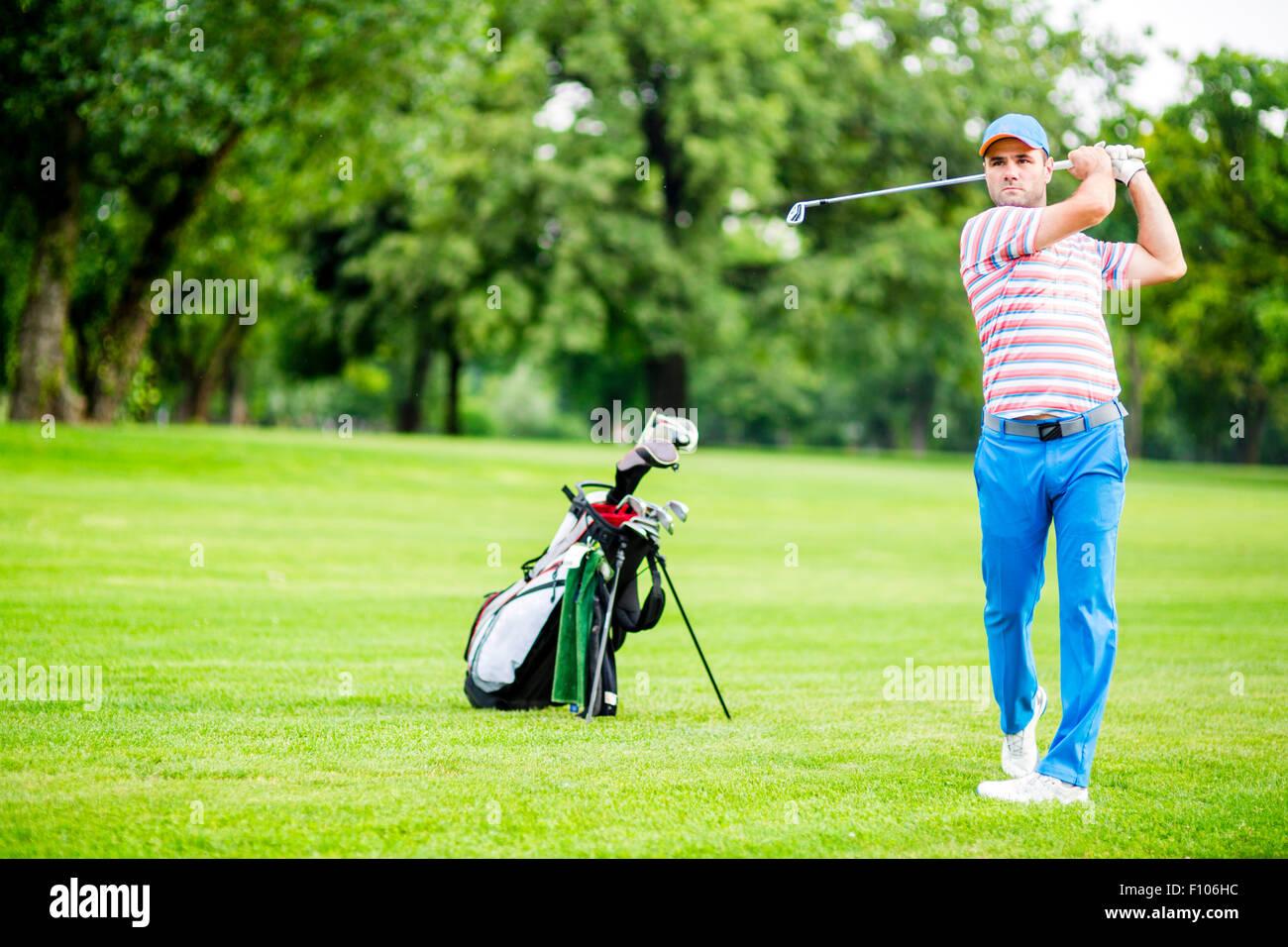 Golfista practicando y concentrar antes y después del disparo durante un día soleado Foto de stock