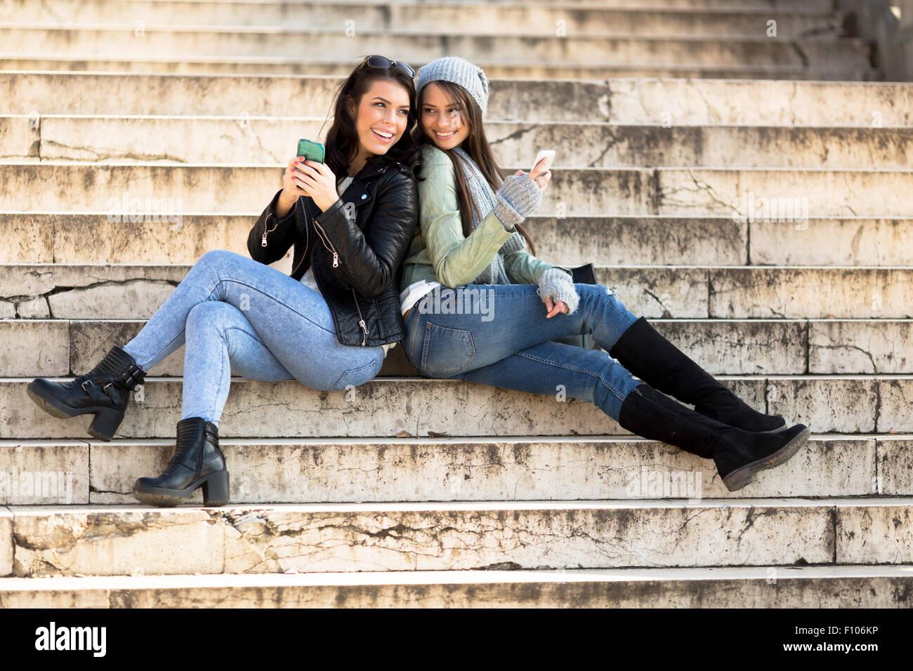 Dos mujeres jóvenes apoyándose unos contra otros en las escaleras y manteniendo los teléfonos celulares Foto de stock