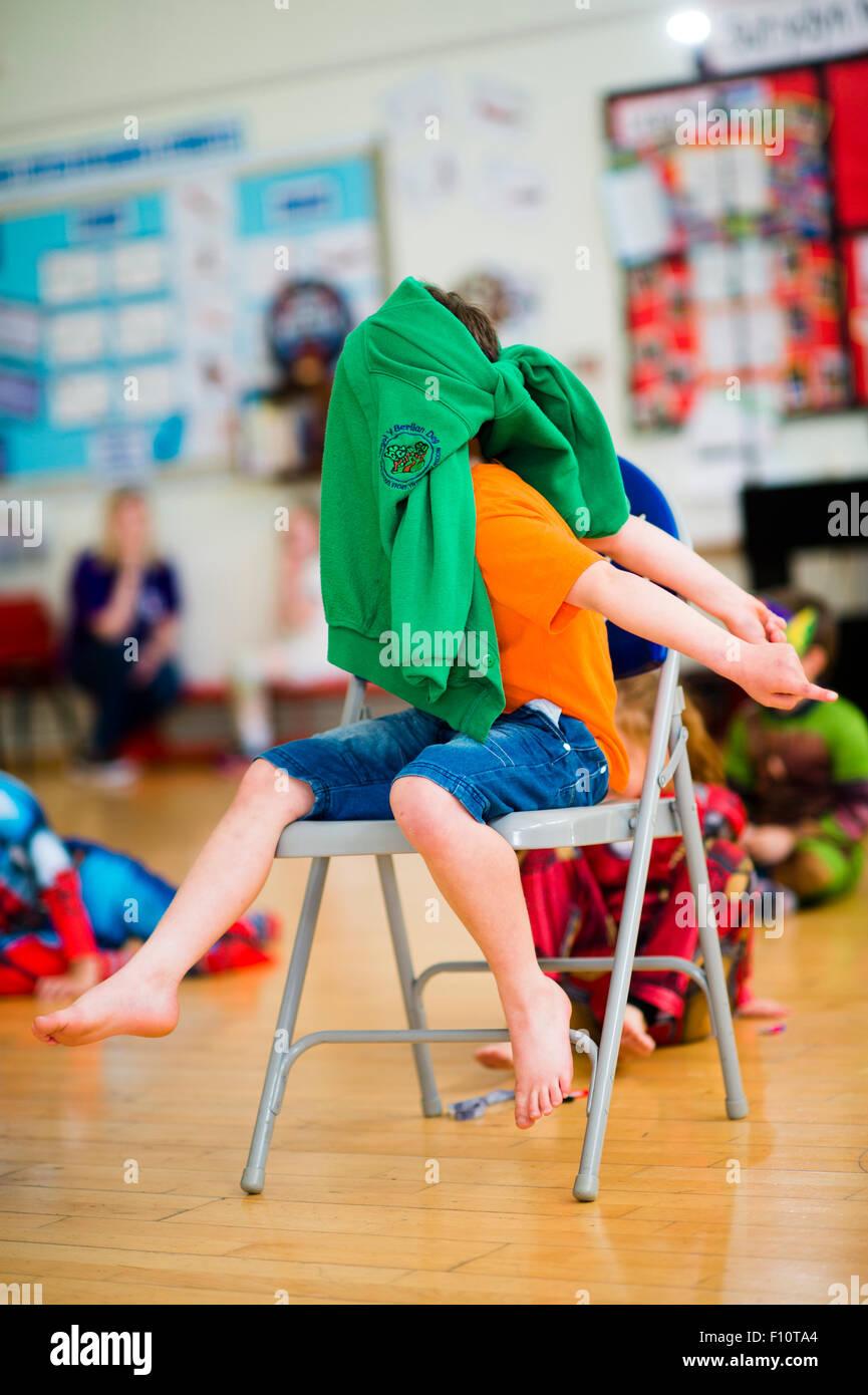 La infancia: niños jugando juegos de interior en una escuela primaria hall, Gales, Reino Unido - El niño tiene un puente atado por su rostro y tiene que adivinar quién ha tocado jhim Foto de stock