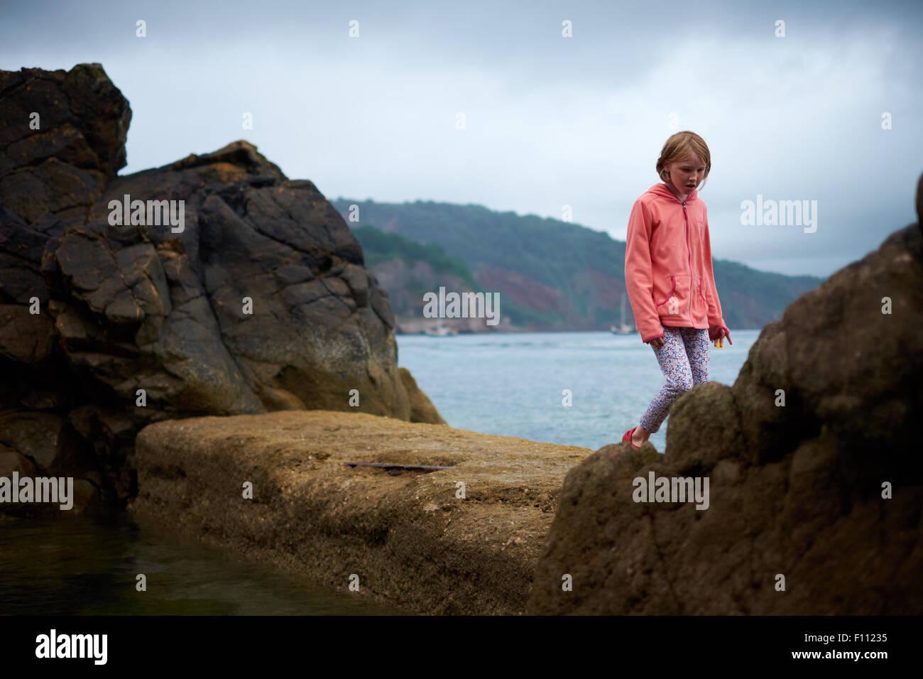 Aventurera niña jugando por el mar en las rocas. Imagen De Stock