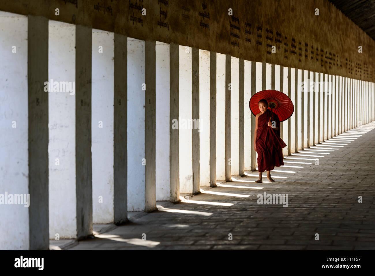 Monje asiático en entrenamiento, llevando una sombrilla en el pasillo Foto de stock