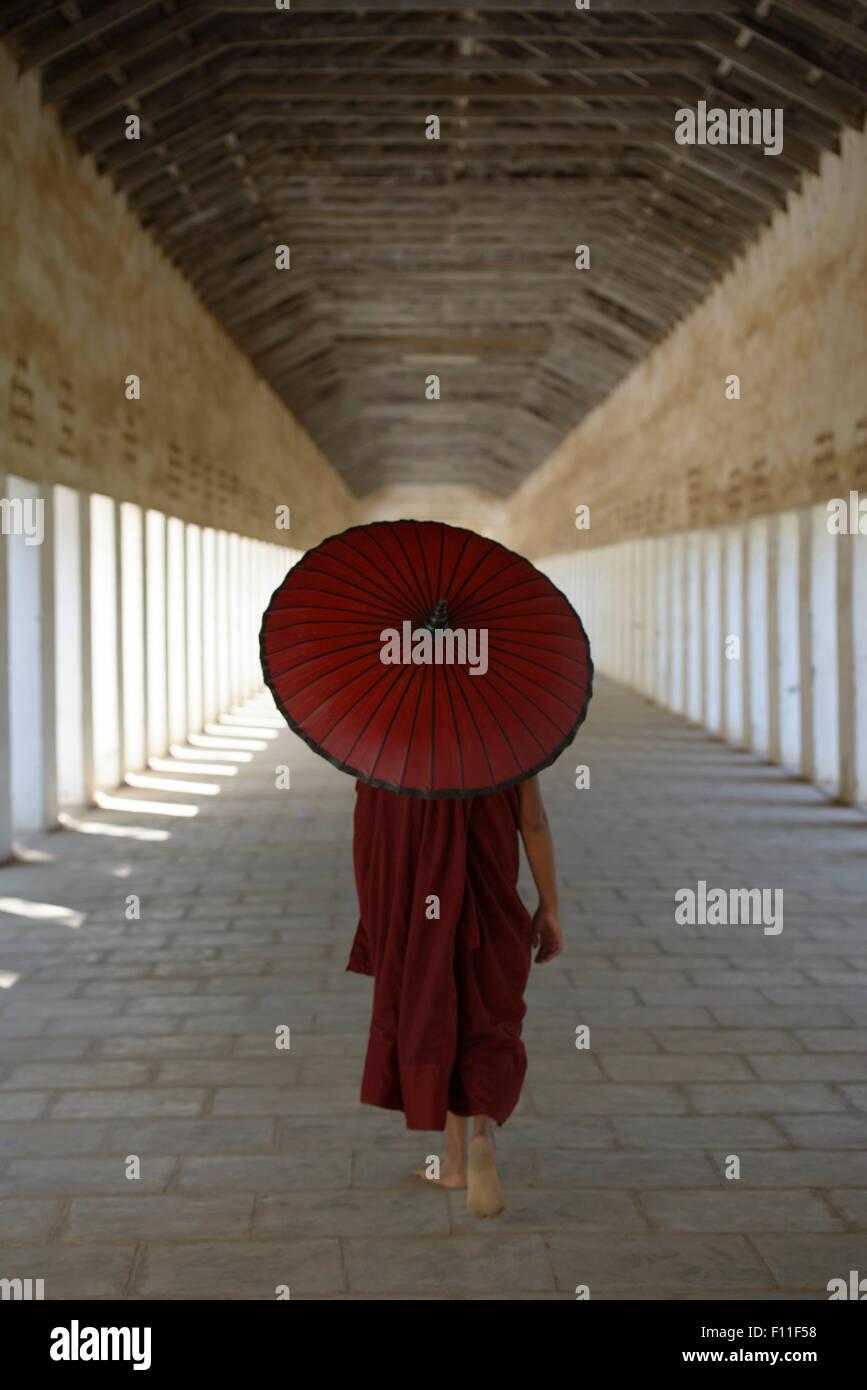 Monje asiático en entrenamiento, llevando una sombrilla en el pasillo Imagen De Stock