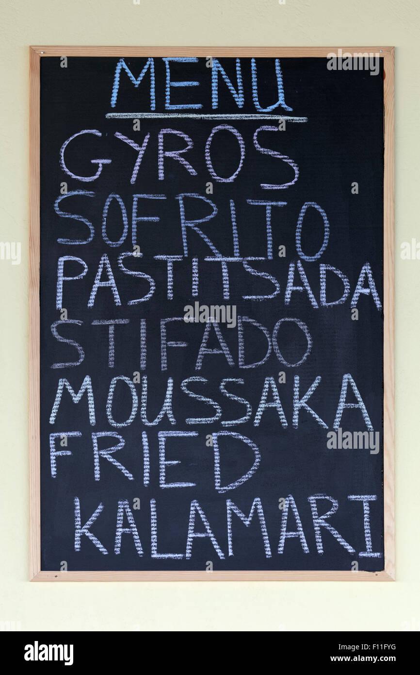 Menú en un pizarrón, platos de la cocina griega, autogiros, el sofrito, la Pastitsada, stifado, musaka Imagen De Stock