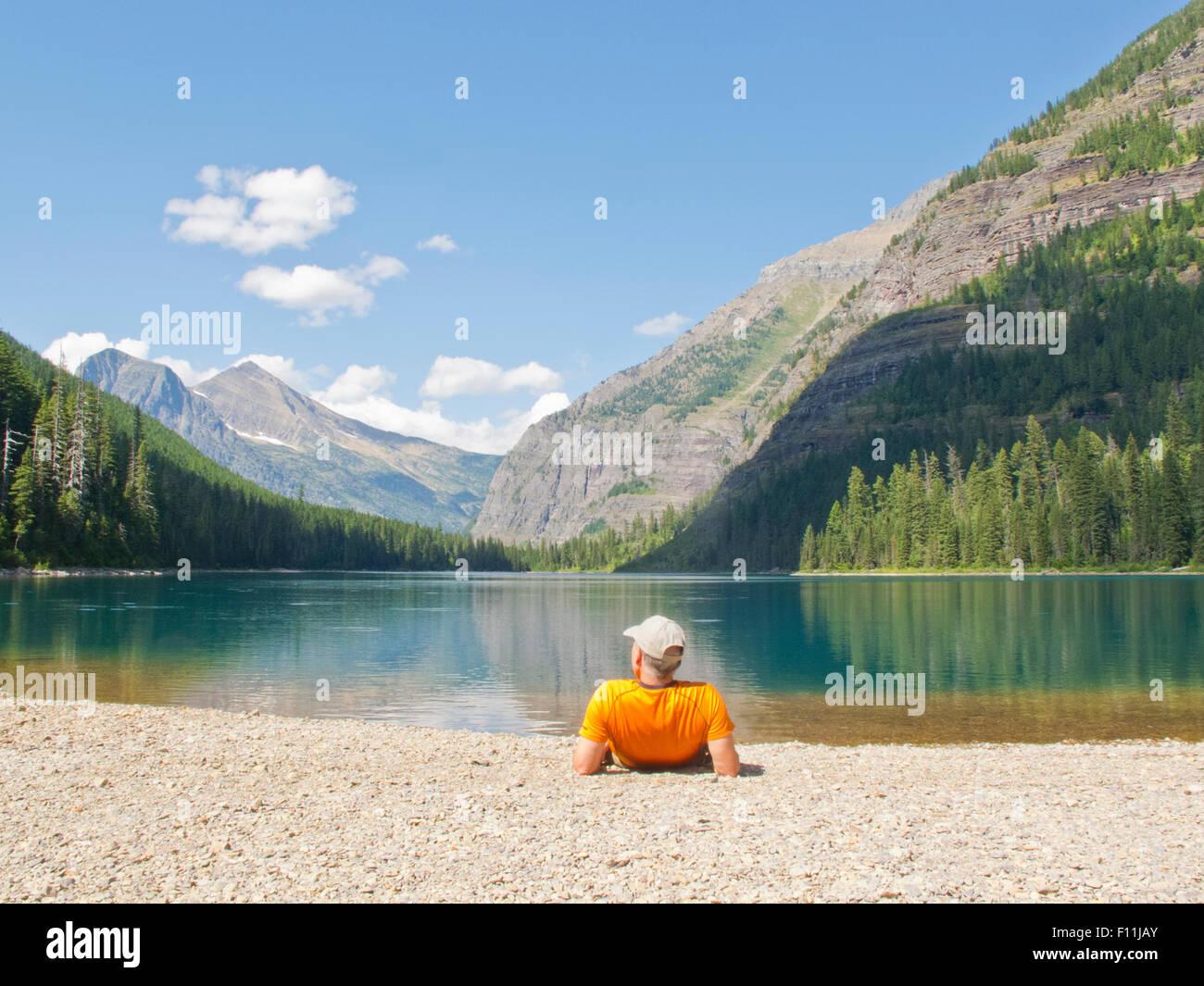 Caminante sentar cerca de lago de montaña, el parque nacional de Glacier, Montana, Estados Unidos Imagen De Stock