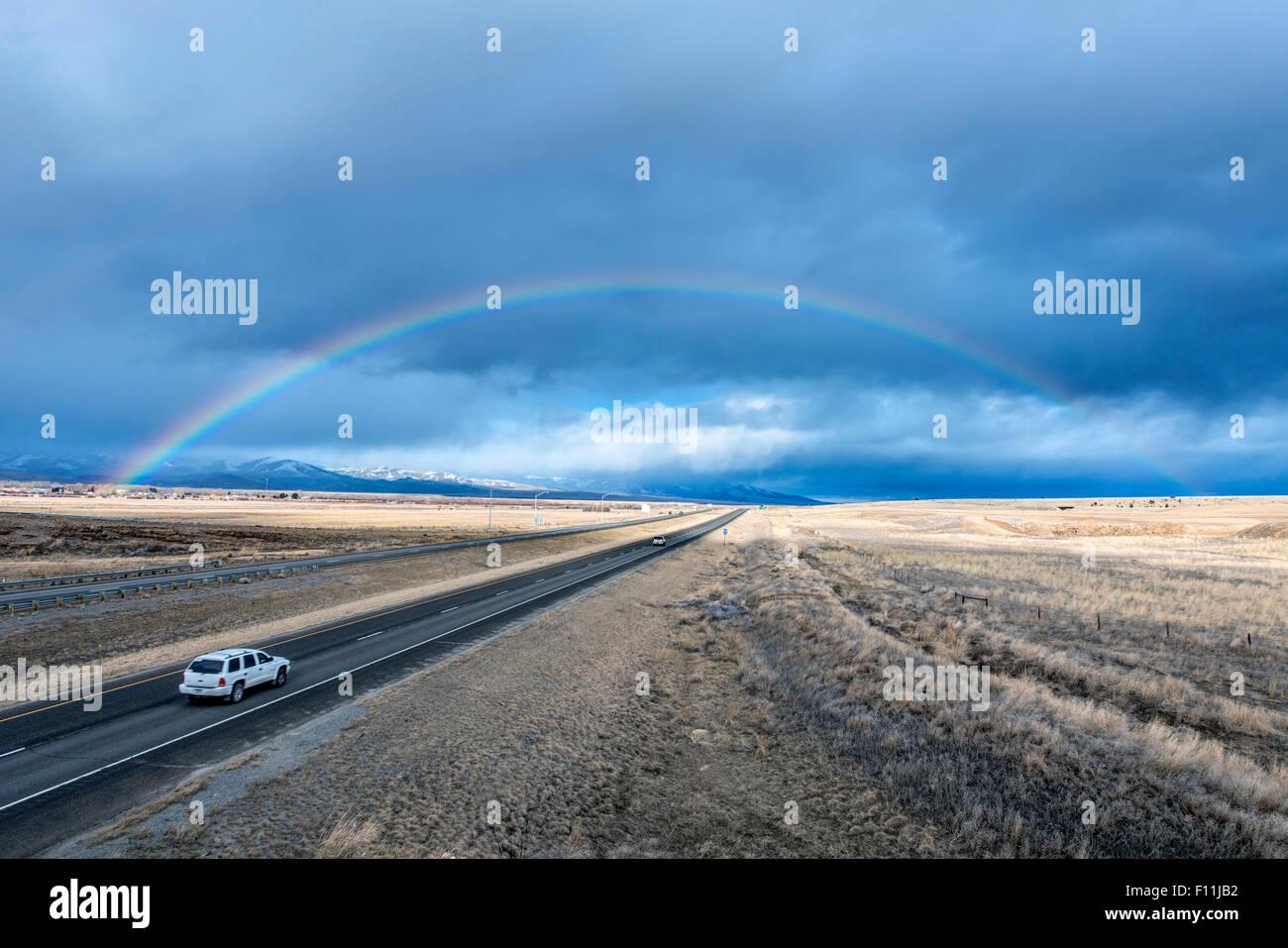 Un alto ángulo de visualización del automóvil a rainbow en remoto camino Imagen De Stock