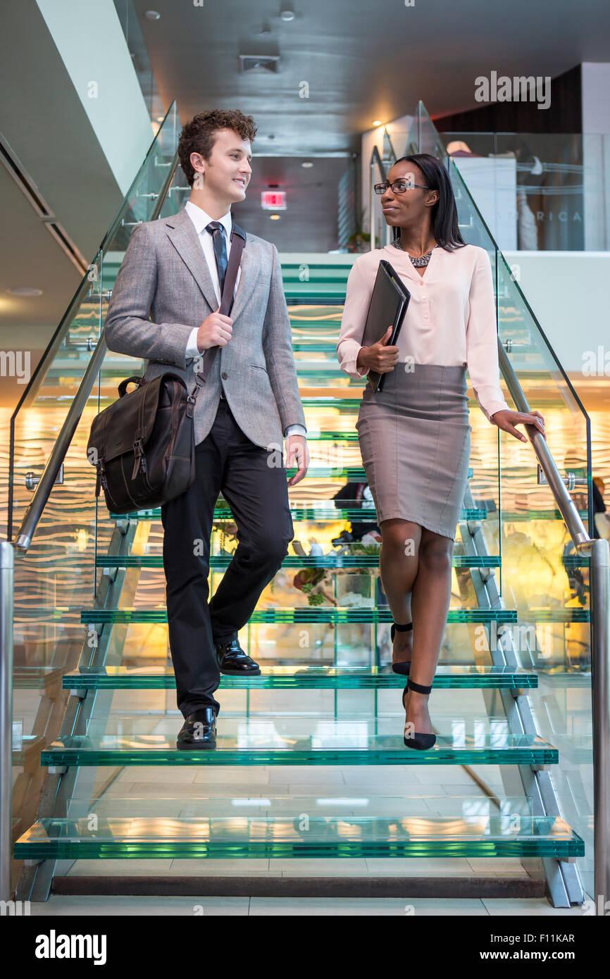 Gente de negocios hablando sobre la escalera de la oficina Foto de stock