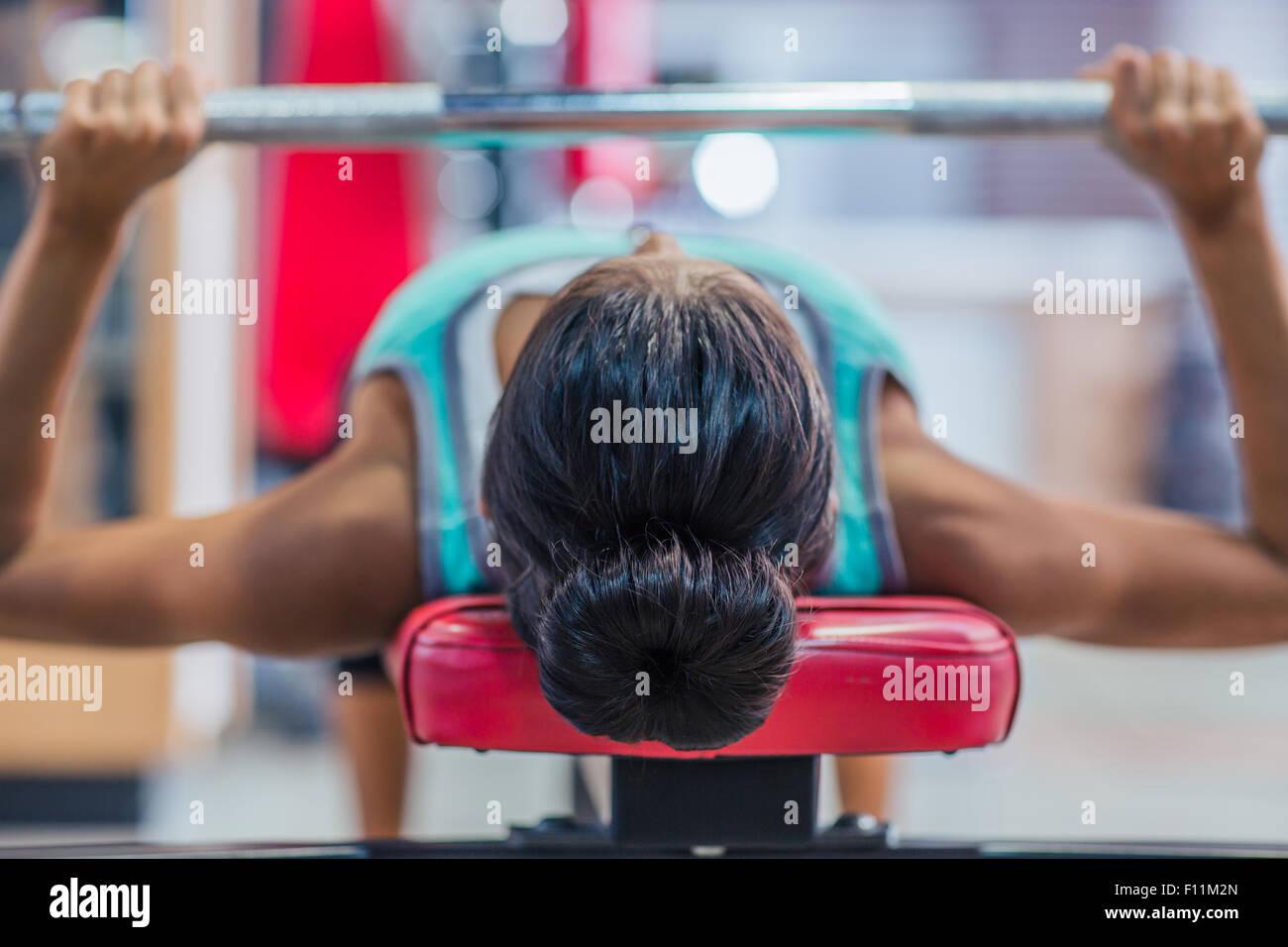Mujer joven con entrenamiento barbell en el banquillo en el gimnasio Imagen De Stock