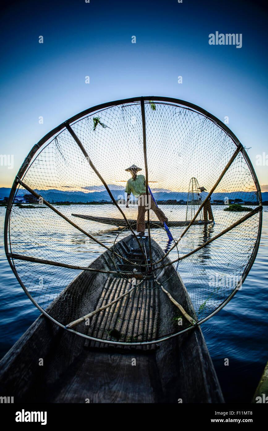 Pescadores asiáticos usando la red de pesca en canoa por el río Imagen De Stock
