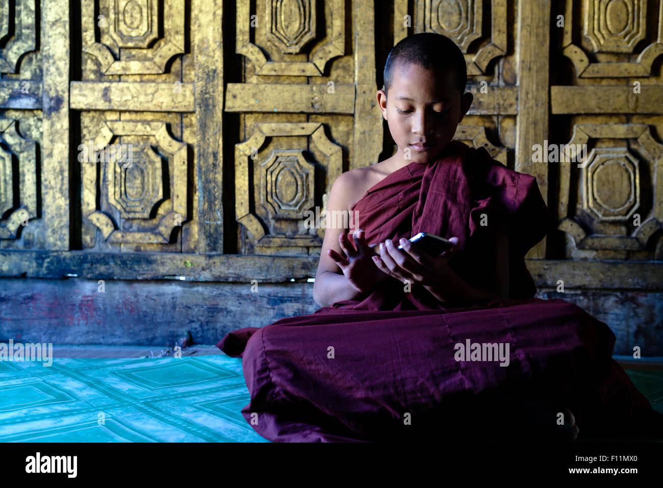 Monje asiático-en-entrenamiento a través de teléfono celular en el templo Imagen De Stock