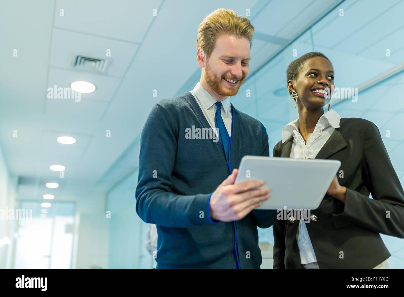Socios y colegas de discutir ideas mostradas en una tableta en un corredor de oficina Imagen De Stock