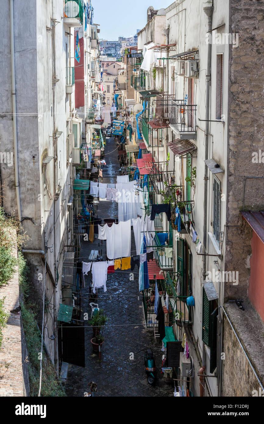 Servicio de lavandería cuelga en tendederos colgando en la calle angosta, entre casas en Nápoles, Italia Foto de stock