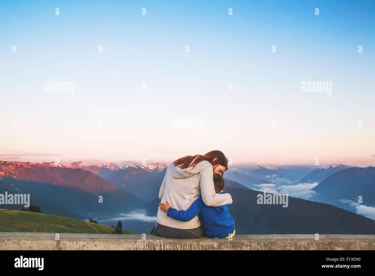 Vista trasera de una mujer sentada sobre una pared abrazando a su hijo Imagen De Stock