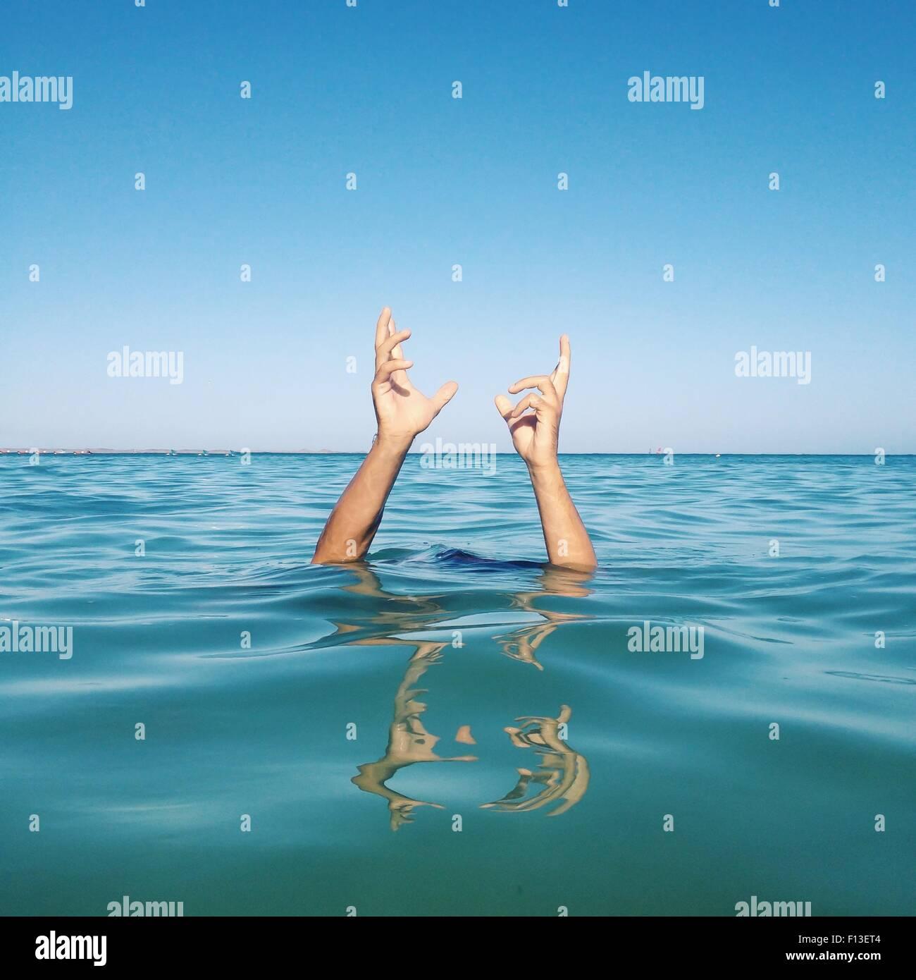 Las manos del hombre saliendo del mar Imagen De Stock
