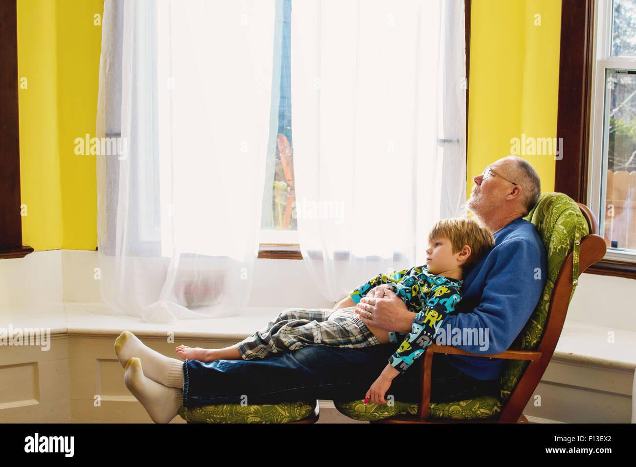 Muchacho sentado en el regazo de su abuelo relajante Imagen De Stock