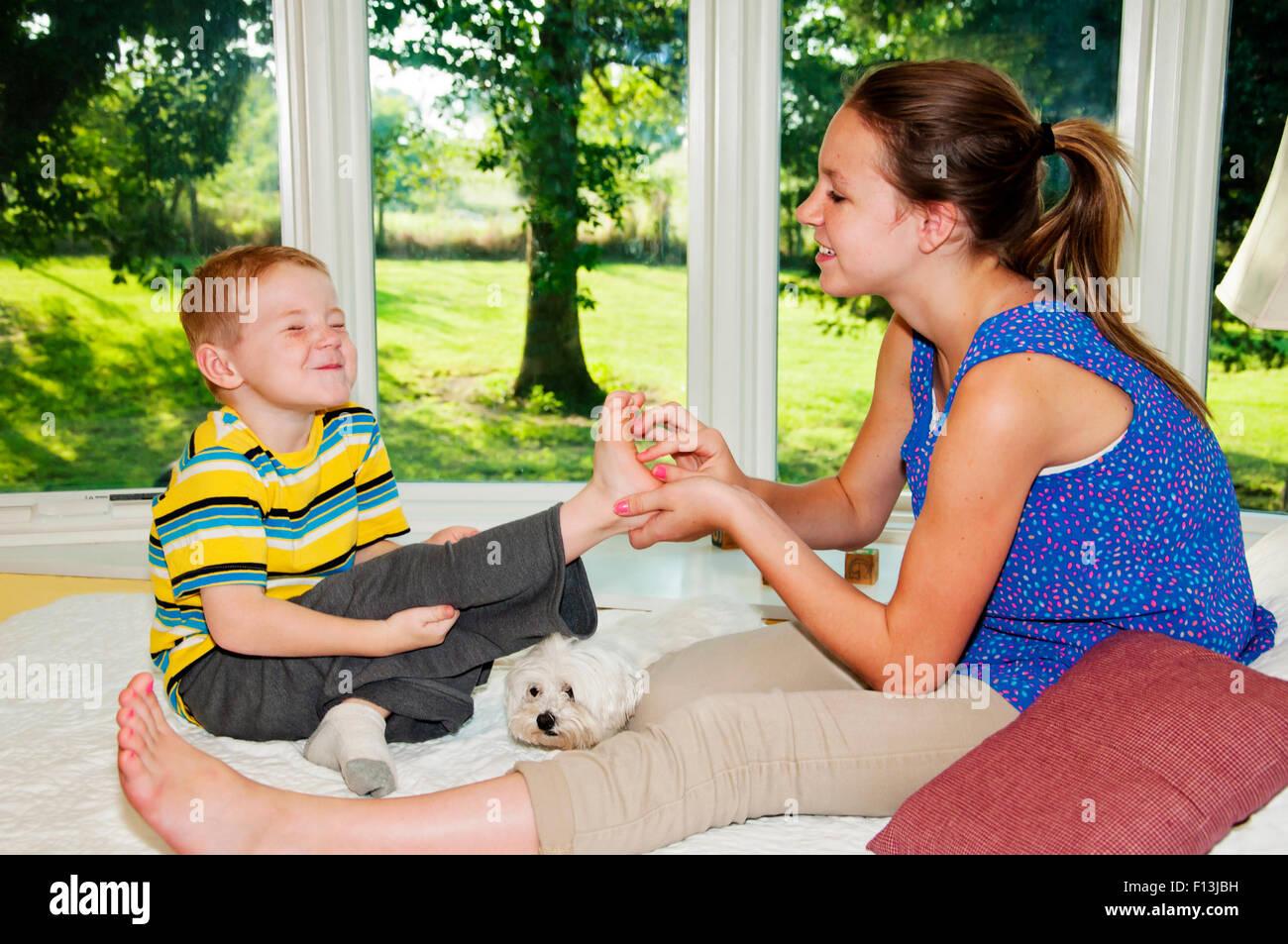 Chico tratando de no reír mientras está de pie tickled Imagen De Stock