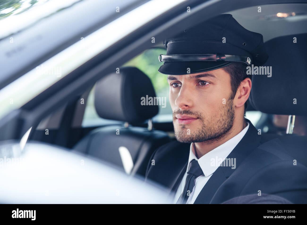 Retrato de un macho guapo sentarse en un coche con chofer Imagen De Stock