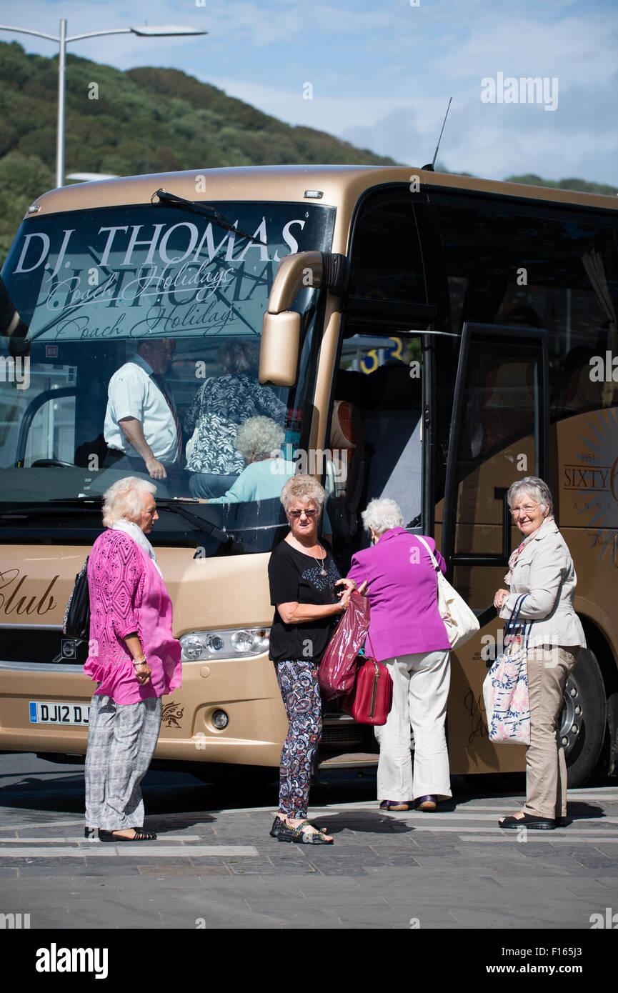Cuatro mujeres mayores turistas subir a un autobús autobús va para un viaje de un día de excursión, Imagen De Stock
