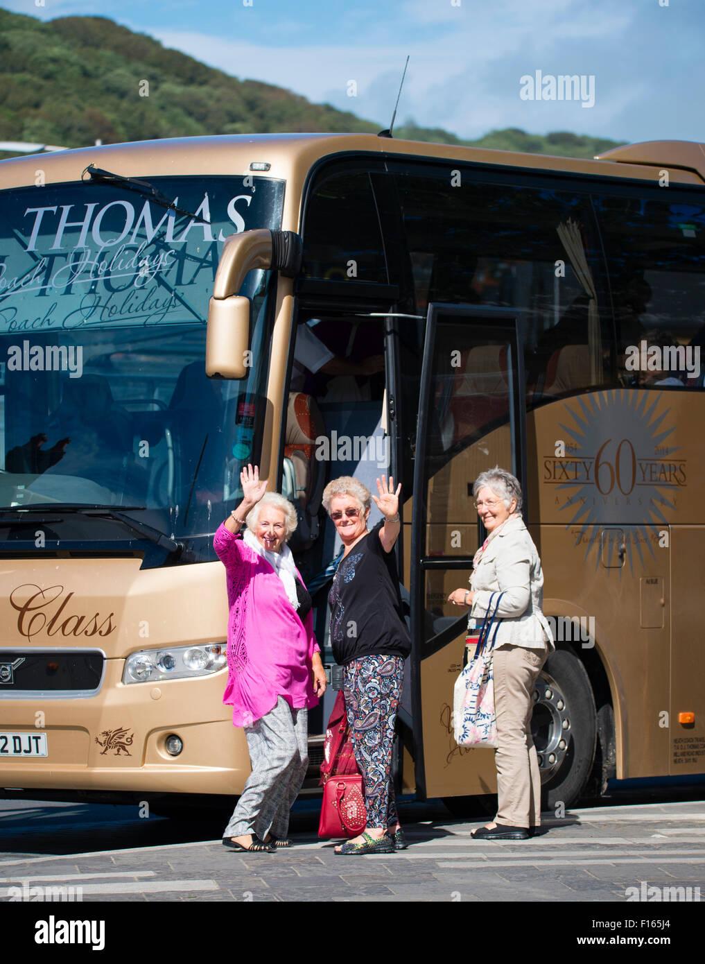 Tres mujeres mayores turistas agitando como entrenador en un autobús que va para un viaje de un día de Imagen De Stock