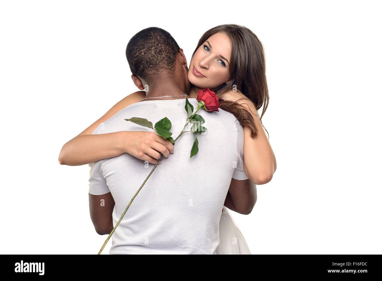 Joven sentimental abrazando a su novio o novia como ella sonríe con ternura hacia abajo en una sola rosa roja Imagen De Stock