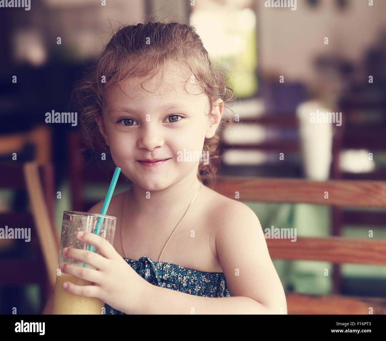 Feliz sonriente chico chica beber jugo fresco de vidrio en el cafe. Tonificado closeup retrato Foto de stock
