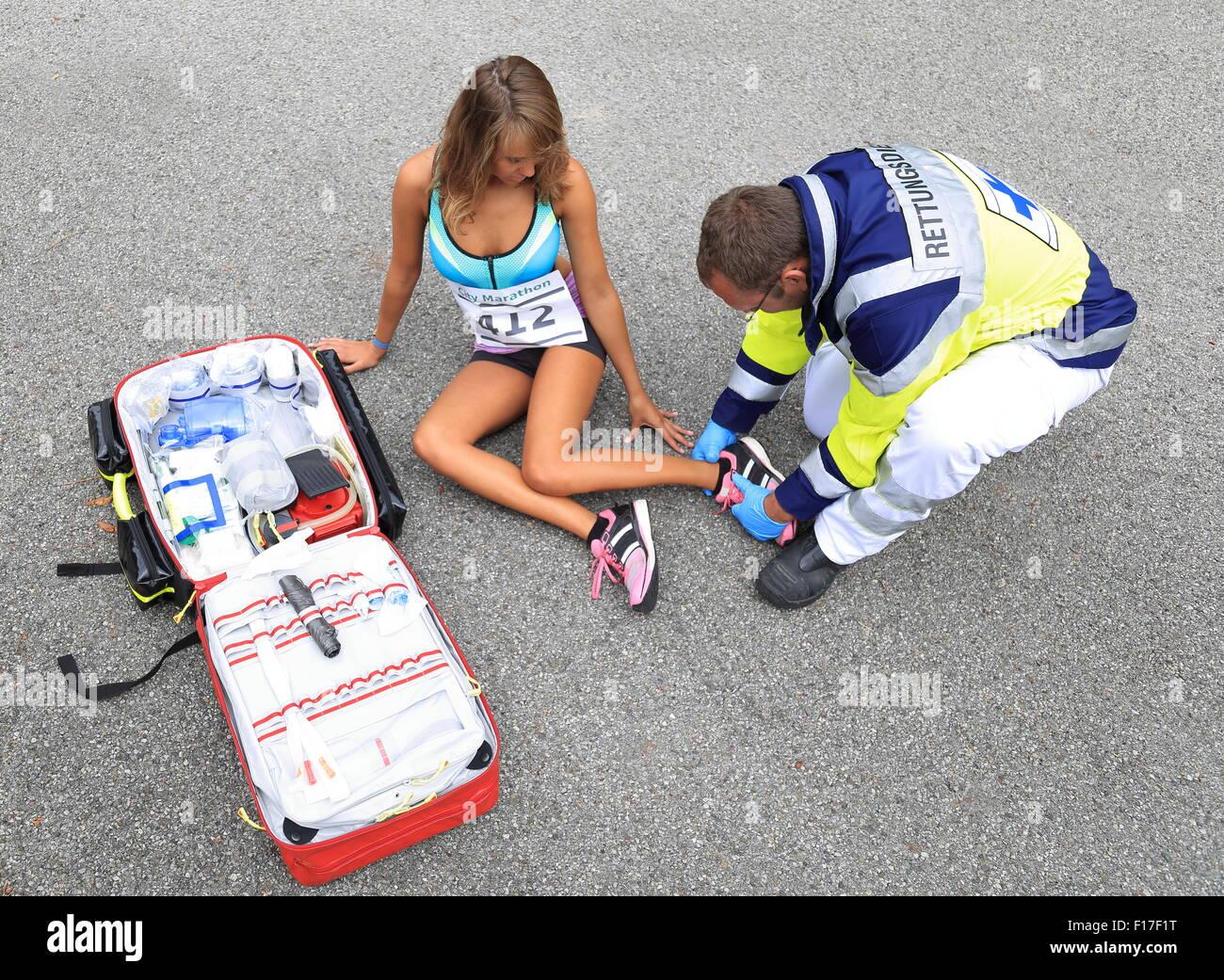 Un paramédico ayudando a corredoras con el tobillo accidente Imagen De Stock