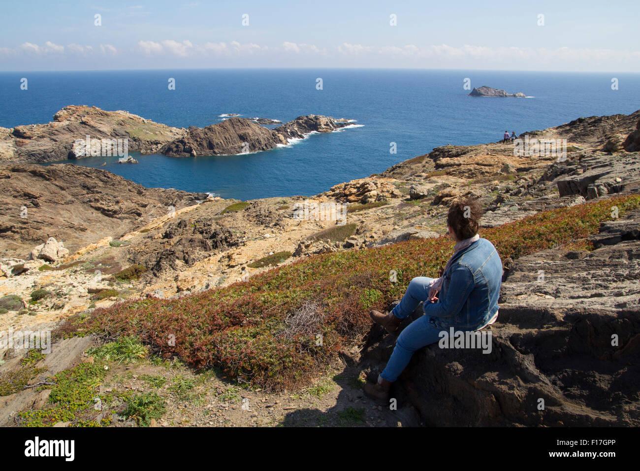 Mujer joven mirando hacia el mar, sentada en una roca Foto de stock