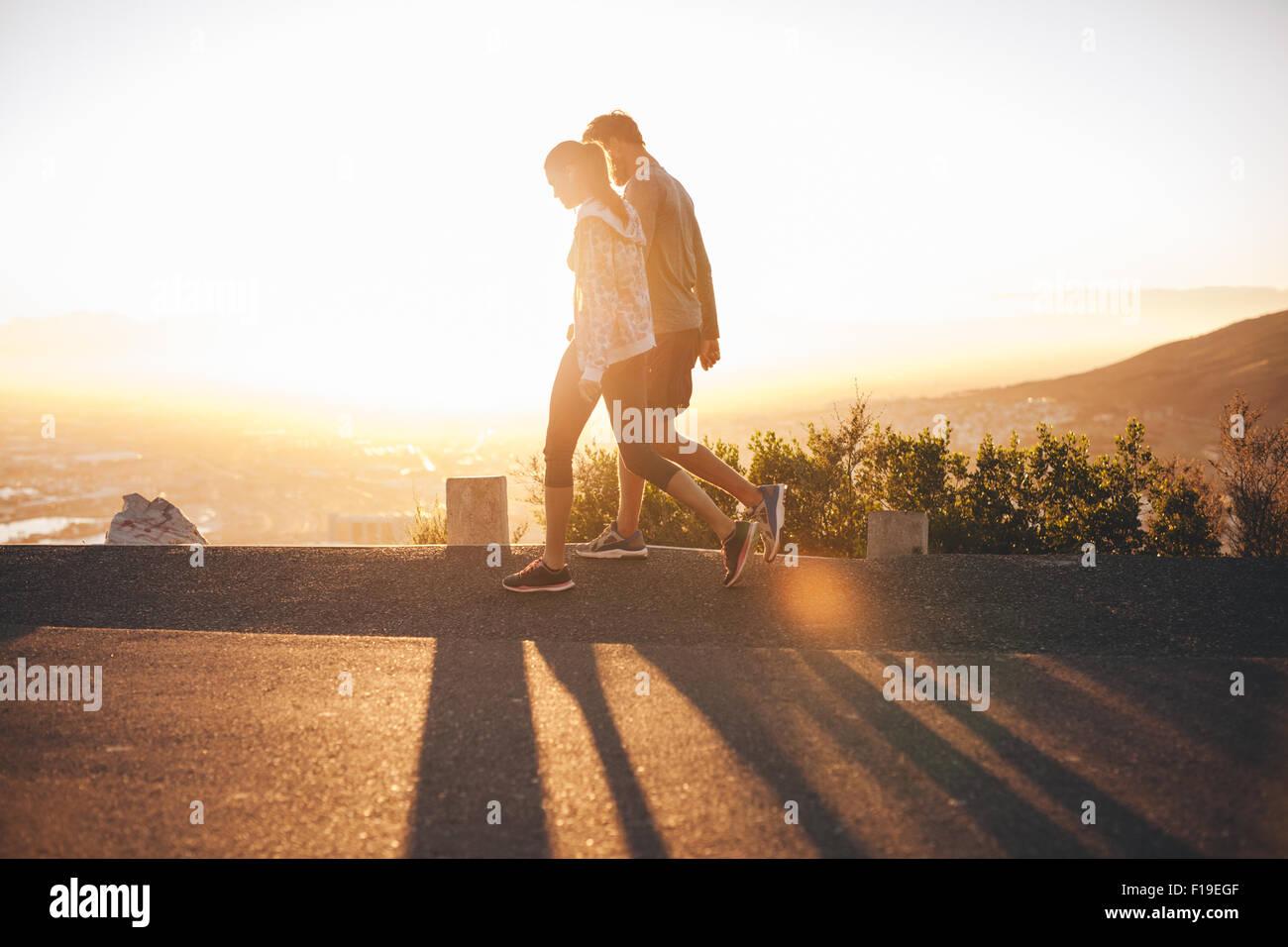 Par de caminar a lo largo de la carretera al amanecer. Par hablando un paseo en Hillside road con luz solar brillante. Foto de stock