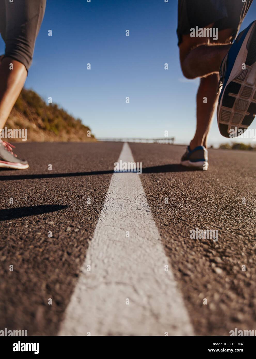 Tiros de ángulo bajo las piernas de los corredores se ejecuta en medio de la carretera. Vista trasera de cerca Imagen De Stock