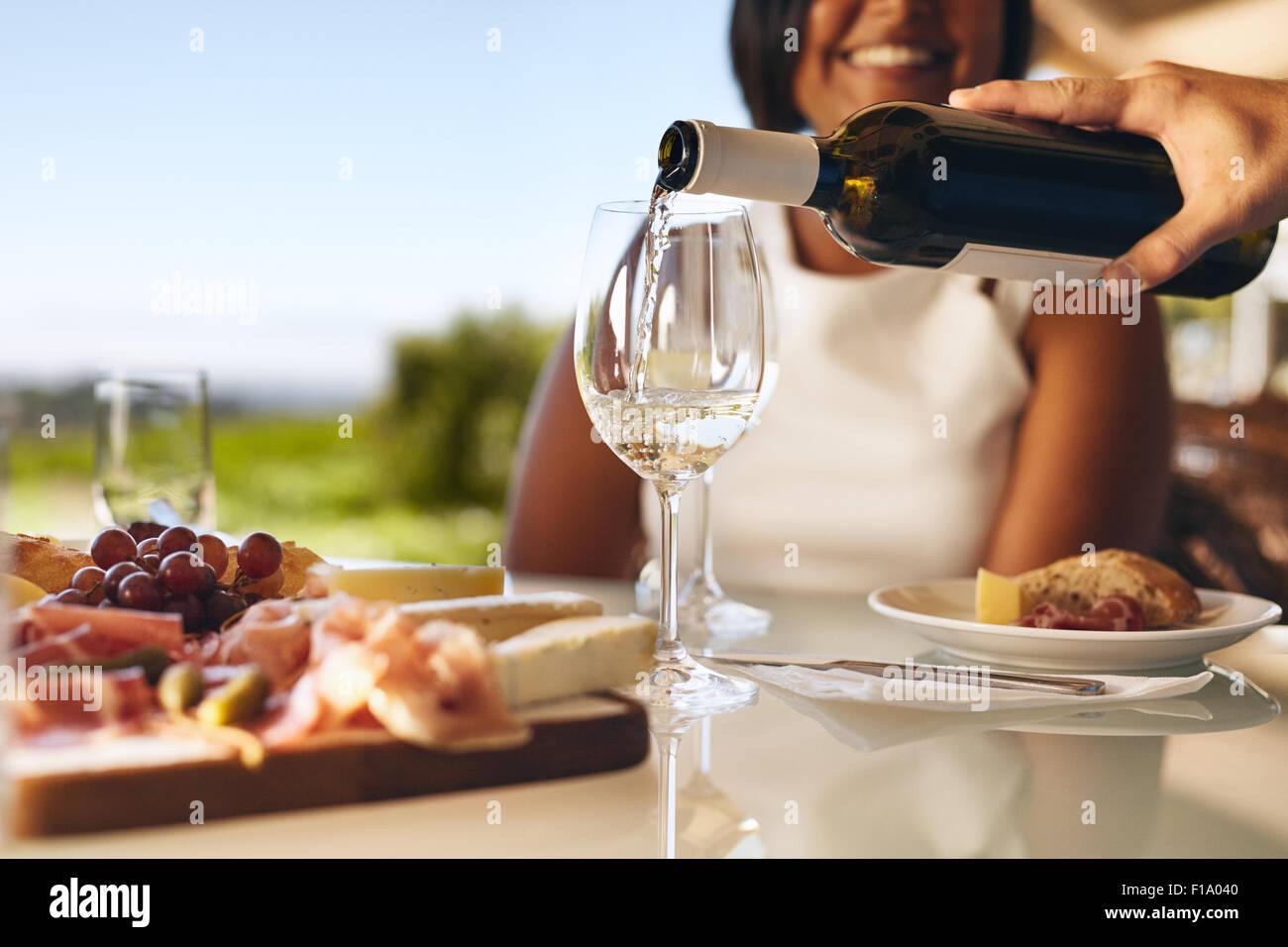 Manos de un hombre verter en dos vasos de vino blanco de la botella con una mujer sonriente en fondo en la bodega. Imagen De Stock